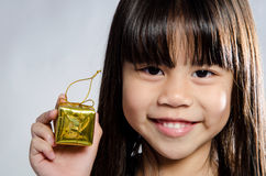 Closeup of Little asian smile girl with gold gift box. On gray background Stock Photos