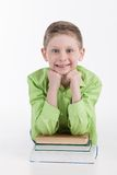 Closeup of little boy leaning on books. Boy waist up looking into camera and smiling Royalty Free Stock Photo