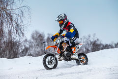 Closeup little boy racers motorcycle rides through snow-covered motocross track Stock Images
