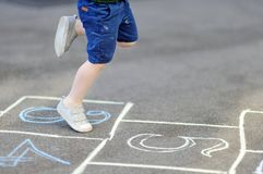 Child playing hopscotch game on playground outdoors on a sunny day. Closeup of little boy`s legs and hopscotch drawn on asphalt. Child playing hopscotch game on Stock Image