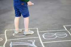 Child playing hopscotch game on playground outdoors on a sunny day. Closeup of little boy`s legs and hopscotch drawn on asphalt. Child playing hopscotch game on Stock Photo