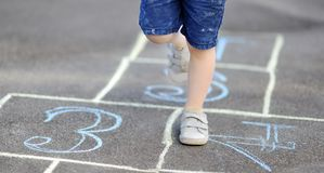 Closeup of little boy`s legs and hopscotch drawn on asphalt stock images