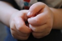 Closeup of a little boys hands with blurry backgound. A Closeup of a little boys hands curled together with blurry backgound Royalty Free Stock Images