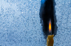 Closeup of little candle flame behind frozen window glass. Closeup photo of little candle flame behind frozen window glass Royalty Free Stock Photography