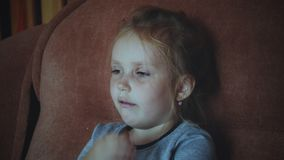 Little sick girl coughs. Closeup of little caucasian girl sitting on sofa and coughing at home stock video footage