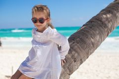 Closeup of little cute girl sitting on palm tree Royalty Free Stock Photo