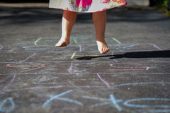 Closeup of little feet in mid air while playing hopscotch Royalty Free Stock Photography