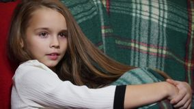 Closeup of a little girl with big eyes sitting in a chair covered with a rug stock footage