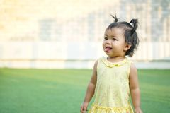 Closeup little girl with cheeky face stand on grass floor in the park background with copy space. Closeup a little girl with cheeky face stand on grass floor in royalty free stock images