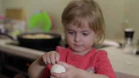 Closeup of a little girl cleans the shell with a boiled chicken egg.  stock footage