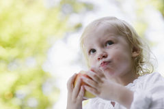 Closeup Of Little Girl Eating Apple Outdoors. Closeup portrait of a little blond girl eating apple outdoors Royalty Free Stock Photography