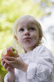 Closeup Of Little Girl Eating Apple Outdoors. Closeup portrait of a little blond girl eating apple outdoors Royalty Free Stock Images