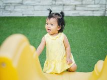 Closeup little girl with funny motion when she play a slider at the playground background royalty free stock images