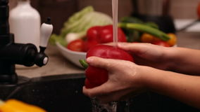 Closeup of little girl hands washing a red bellpepper stock video