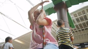 Closeup Little Girl Has Fun on Swing in Shopping Centre stock footage