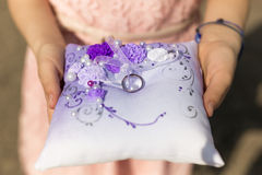 Closeup of little girl holding cushion with wedding rings Stock Photos