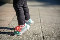 Little girl with sneakers and leggins training outdoors. Closeup of little girl legs with sneakers and black leggins training outdoors Royalty Free Stock Image