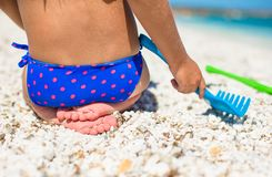 Closeup of little girl legs on tropical beach with Royalty Free Stock Photo