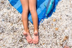Closeup of little girl legs on tropical beach with Stock Image