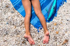 Closeup of little girl legs on tropical beach with Royalty Free Stock Photos