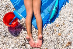 Closeup of little girl legs on tropical beach with Stock Images
