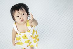Closeup little girl look like she want something on white tiled floor textured background with copy space royalty free stock images