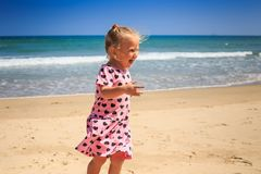 Closeup Little Girl in Pink Cries with Joy by Wave Surf. Closeup little blond girl with pigtails in pink dress cries with joy by azure ocean wave surf on beach Royalty Free Stock Image