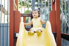 Closeup little girl play a slider at the playground background royalty free stock image