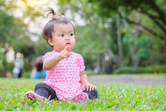 Closeup little girl sit on grass floor in the park with sun light background in cute motion stock images