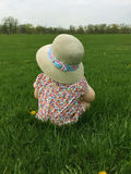 Closeup of little girl sitting in grass at a park wearing a straw hat and looking off into distance Stock Images