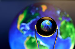 Closeup of a Little Glass ball reflecting the planet earth Royalty Free Stock Photos