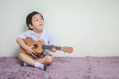 Closeup a little kid in student uniform play ukulele on carpet with copy space stock photo