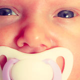 Closeup of little newborn lying with teat in mouth Royalty Free Stock Images