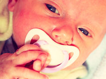 Closeup of little newborn lying with teat in mouth Stock Photo