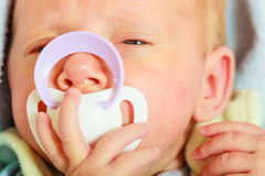 Closeup of little newborn lying with teat in mouth. Infant care, beauty of childhood concept. Little newborn baby lying calmly in bed with teat in mouth, closeup Stock Photos