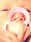 Closeup of little newborn lying with teat in mouth. Infant care, beauty of childhood concept. Little newborn baby lying calmly in bed with teat in mouth, closeup Royalty Free Stock Photos