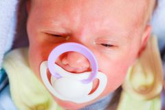 Closeup of little newborn lying with teat in mouth. Infant care, beauty of childhood concept. Little newborn baby lying calmly in bed with teat in mouth, closeup Stock Image