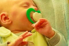 Closeup of little newborn sleeping with teat in mouth Stock Photo