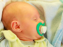 Closeup of little newborn sleeping with teat in mouth Royalty Free Stock Photos