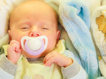 Closeup of little newborn sleeping with teat in mouth Stock Photography