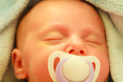 Closeup of little newborn sleeping with teat in mouth. Infant care, beauty of childhood concept. Little newborn baby sleeping calmly in bed with teat in mouth Stock Image