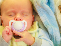 Closeup of little newborn sleeping with teat in mouth. Infant care, beauty of childhood concept. Little newborn baby sleeping calmly in bed with teat in mouth Stock Photo