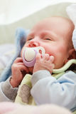 Closeup of little newborn sleeping with teat in mouth. Infant care, beauty of childhood concept. Little newborn baby sleeping calmly in bed with teat in mouth Royalty Free Stock Image