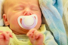 Closeup of little newborn sleeping with teat in mouth. Infant care, beauty of childhood concept. Little newborn baby sleeping calmly in bed with teat in mouth Royalty Free Stock Photos
