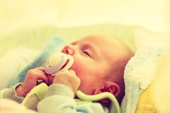 Closeup of little newborn sleeping with teat in mouth. Infant care, beauty of childhood concept. Little newborn baby sleeping calmly in bed with teat in mouth Royalty Free Stock Images