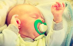 Closeup of little newborn sleeping with teat in mouth. Infant care, beauty of childhood concept. Little newborn baby sleeping calmly in bed with teat in mouth Stock Images