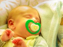 Closeup of little newborn sleeping with teat in mouth. Infant care, beauty of childhood concept. Little newborn baby sleeping calmly in bed with teat in mouth Royalty Free Stock Photo