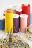 Closeup of a little pillow with needles. Threads in many colors on background. Focus on needles. Meter also visible Stock Image