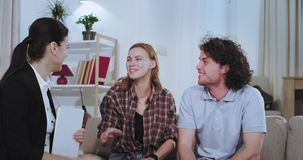 Closeup in a living room charismatic couple make a deal with their house agent to rent a house they shaking hands with. Real estate agent and happy couple stock footage
