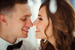 Closeup of lovely wedding couple touching eahc other noses.  Royalty Free Stock Image